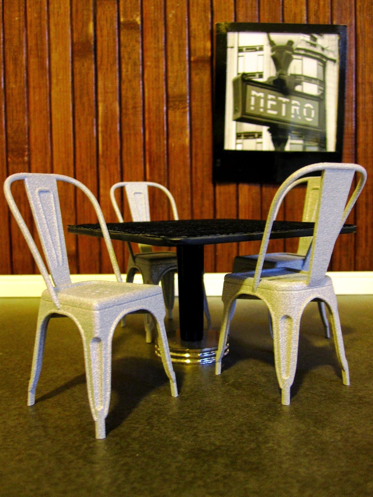 A dolls house miniature scene of four Xavier Pauchard Model A chairs around a cafe table.