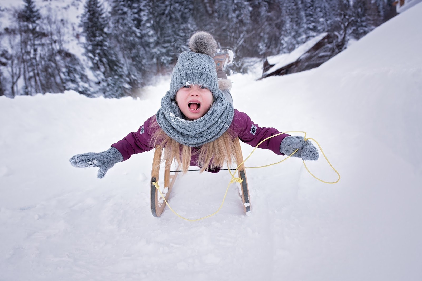 What is the best way to keep our kids warm - child on a toboggan in the snow