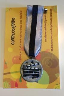 Medalla en fimo de una claqueta sobre un rollo de película