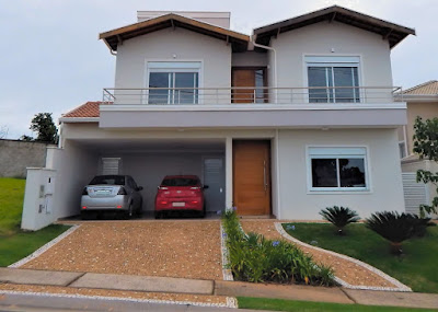Na fachada desta casa, dois volumes se destacam do corpo central, criando um sistema derivado na cobertura de duas águas.