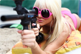 Lady with sunglasses and bikini pointing a paintball gun