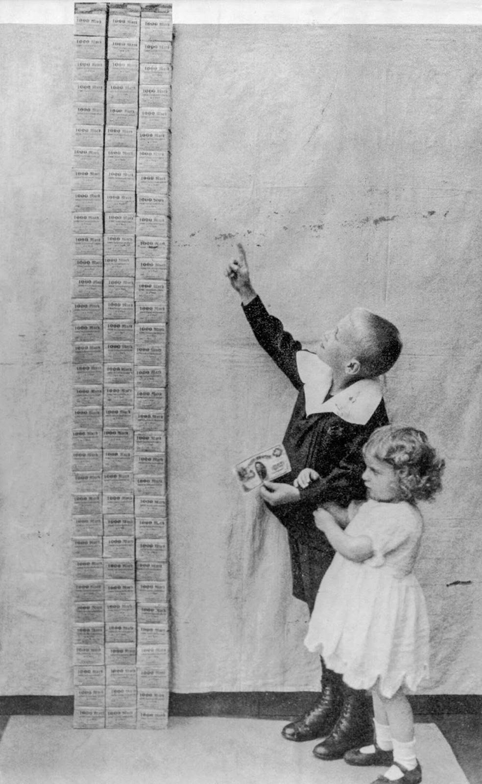 Children stand next to a tower of 100,000 marks, equal in value to one US dollar. 1923.