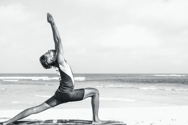 Black and White Image of a Man Practicing Yoga on a Beach