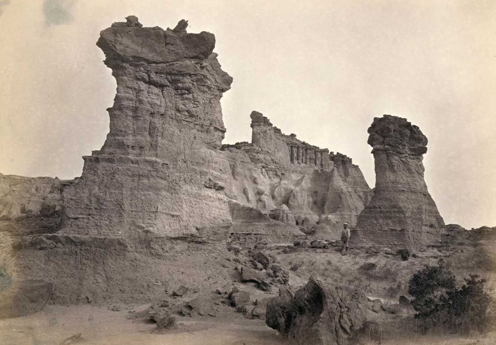 Rock formations in the Washakie Badlands, Wyoming, in 1872. A survey member stands at lower right for scale.