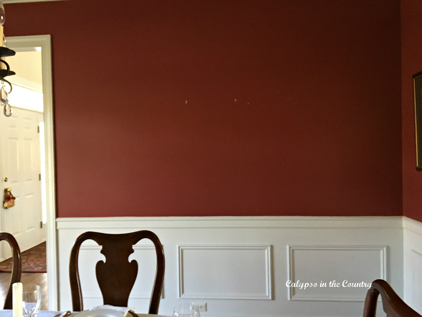 Red dining room wall with nail holes