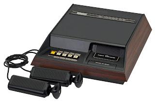 Imagen de la videoconsola doméstica Fairchild Channel F de Fairchild Semiconductor International Inc. de 1976. Se trata de una especie de cajón oscuro con una fila de botones, una ranura de cartuchos y dos extraños mandos en forma de detonador de bomba...
