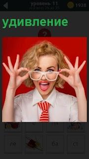Девушка в очках неожиданно удивляясь снимает очки. Одета в белую блузку с красным галстуком