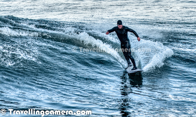 Photo Walk around San Francisco was one of the highlight of my recent trip to US and our last spot during the PHOTO WALK was Surfing point under Golden Bridge. This Photo Journey shares some of the moments captured under Golden Bridge of San Francisco. Surfing is a surface water sport in which the wave rider, 'surfer', rides on the forward face of a wave. Waves suitable for surfing are found primarily in the ocean, but can be found in some lakes, in rivers in the form of a standing wave. Surfing can also be done in artificial water sources such as wave pools and boat wakes. The term 'surfing' refers to the act of riding a wave and not the form in which the wave is ridden After having lunch at De Young Museum, we moved to the bottom of Golden Bridge where lot of surfers were getting ready for surfing in Pacific Ocean. They were carrying surfing boards in their cars and changing the cloths to gear up for a great adventure in water. Most of the these photographs are cropped versions, as they were surfing at a significant distance from shoreline.  This is first time that I saw people doing surfing in front of me and even when chilled wind was blowing all around the San Francisco town. It was a cloudy day and most of us were wearing multi-layered cloths. After coming back from this point, I realized that I should have made a video of these folks surfing in the ocean as action is not well captured in these photographs. It's really amazing to see surfers playing so well with high waves in ocean.Surfing can be done on various equipments including surfboards, longboards, Stand Up Paddle boards (SUP's), bodyboards, wave skis, skimboards, kneeboards, surf mats and macca's trays. Surfers of different age groups were there at Golden Bridge to enjoy the day... After mild rains in the morning, sun was out.Three major subdivisions within sitting-up surfing are longboarding, shortboarding, and stand up paddle surfing (SUP), reflecting differences in board design, including surfboard length, riding style and the kind of wave that is ridden.Surfers represent a diverse culture based on riding the waves. Some people practice surfing as a recreational activity while others make it the central focus of their lives. Within the United States, surfing culture is most dominant in Hawaii and California because these two states offer the best surfing conditions. Some historical markers of the culture included the woodie, the station wagon used to carry surfers' boards, as well as boardshorts, the long swim shorts typically worn while surfing.Several of San Francisco's parks and nearly all of its beaches form part of the regional Golden Gate National Recreation Area, one of the most visited units of the National Park system in the United States with over 13 million visitors a year. Among the GGNRA's attractions within the city are Ocean Beach, which runs along the Pacific Ocean shoreline and is frequented by a vibrant surfing community.