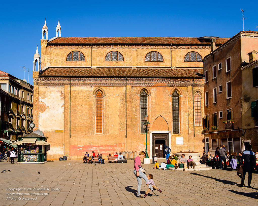 a photo of a mother and child playing in a sunny square in venice italy