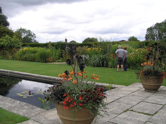 formalny staw, kamienna nawierzchnia w ogrodzie, donice w ogrodzie