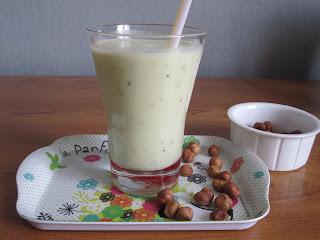 Verre de smoothie banane kiwi et vanille sur un plateau avec des noisettes entières