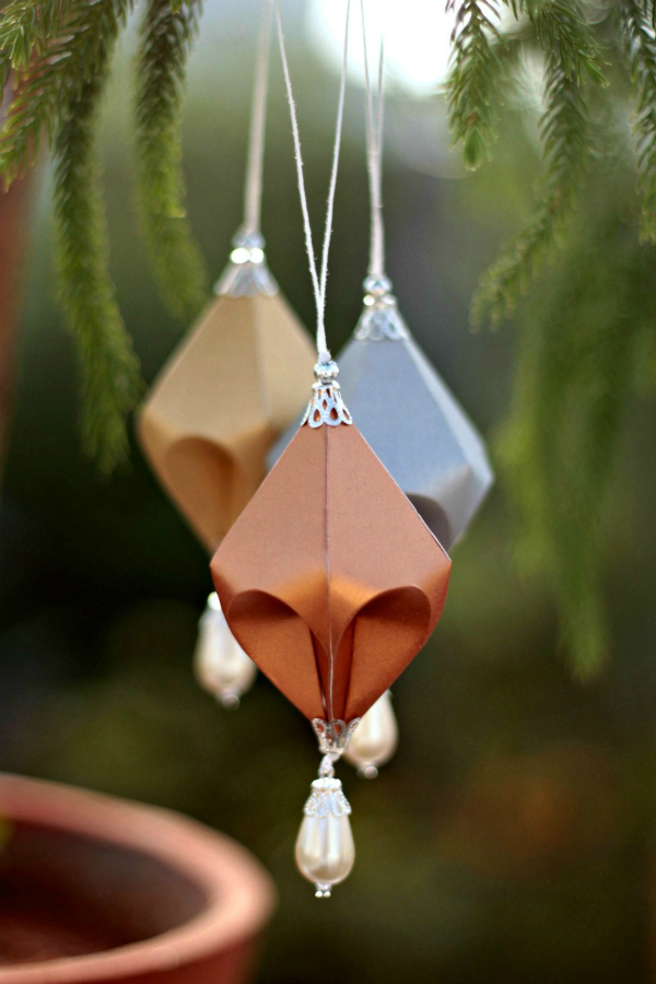 Three metallic paper ornaments hanging on tree