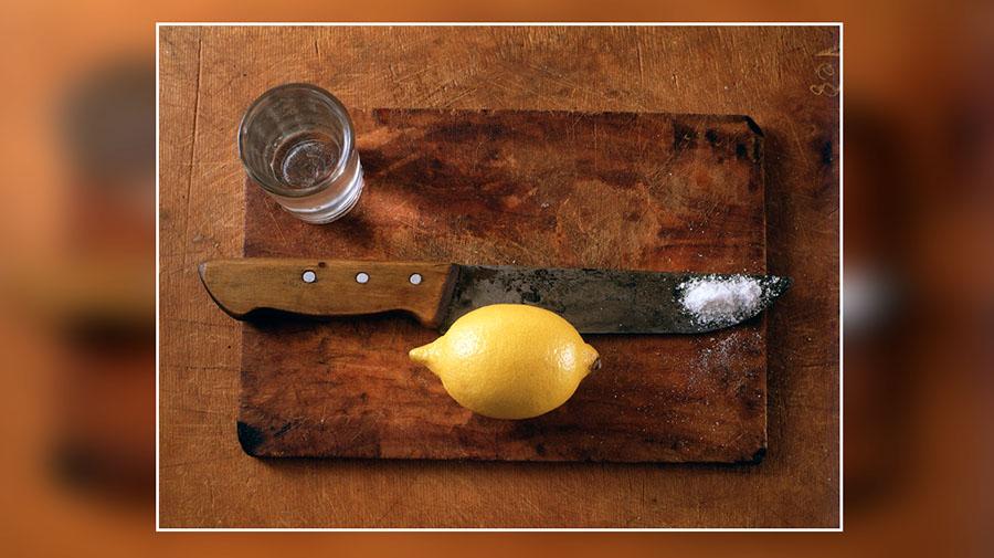 Текила и лимон на разделочной доске