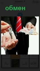 происходит обмен ключей на деньги мужчиной в галстуке