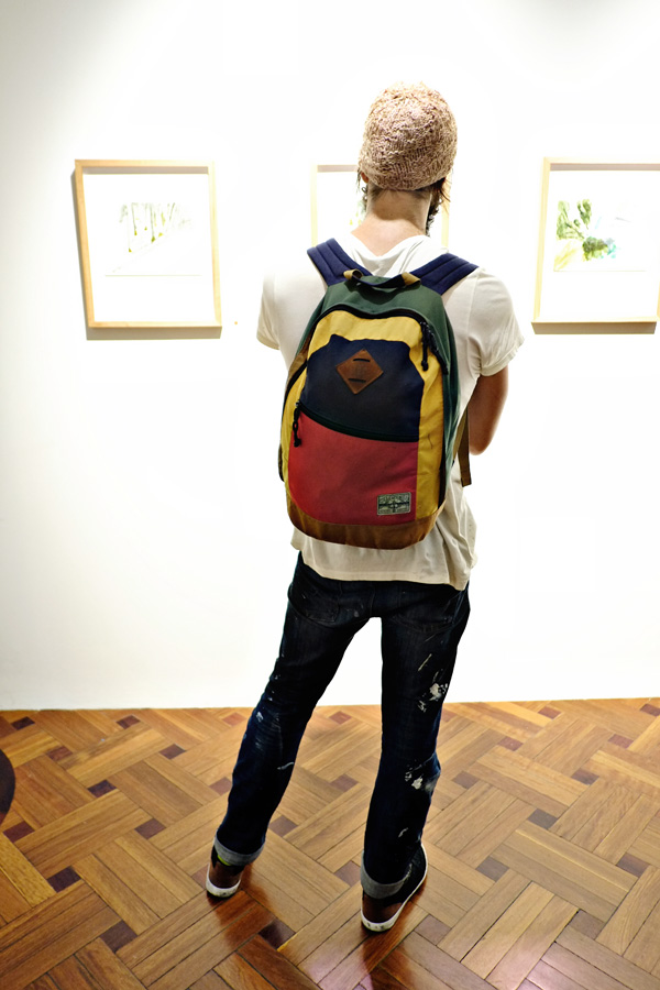 Colourful backpakc, paint smeared jeans  and woollen beanie. Photography by Kent Johnson for Street Fashion Sydney.