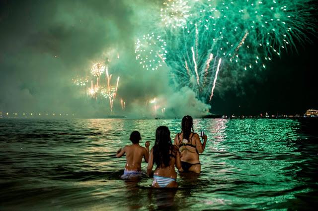 Люди дивляться святковий феєрверк з води на пляжі Копакабана.
