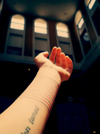 Vermelho e preto, braçadeiras de envoltório em torno do utente pulso neste tatuagem.