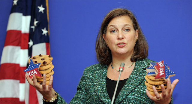 Victoria Nuland pictured with her hands full of 'USA' themed cookies