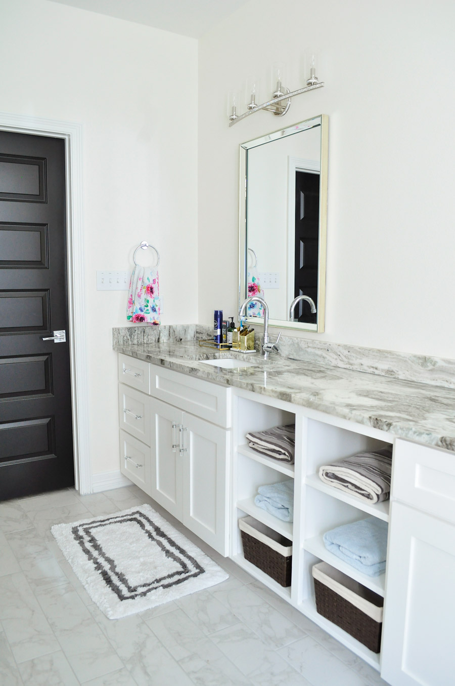 An alabaster white bathroom with black interior doors and chrome and mirrored finishes.