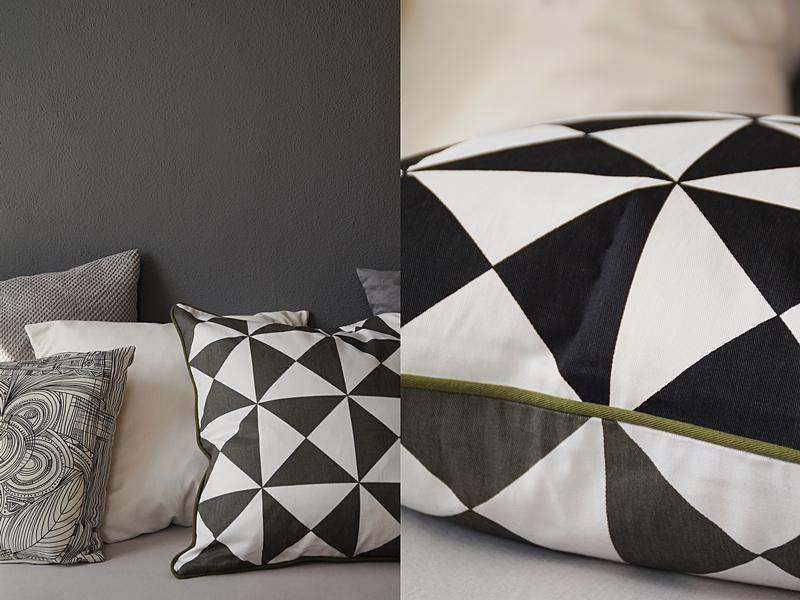 Schlafzimmer in Grautönen mit vielen Kissen
