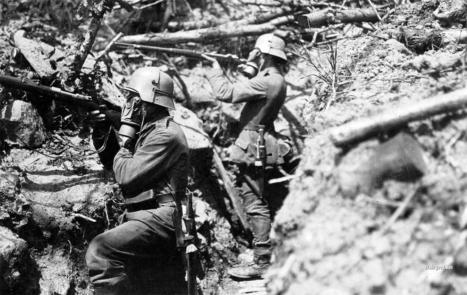 German infantrymen from Infanterie-Regiment Vogel von Falkenstein Nr.56 adopt a fighting pose in a communication trench somewhere on the the Western Front. Both soldiers are wearing gas masks and Stahlhelm helmets, with brow plate attachments called stirnpanzers. The stirnpanzer was a heavy steel plate used for additional protection for snipers and raiding parties in the trenches, where popping your head above ground for a look could be lethal move.