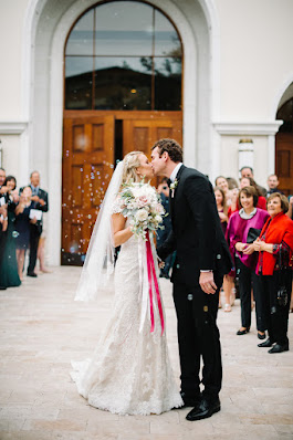 bride and groom leaving venue and kiss