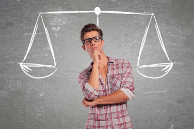 A man considers a balancing scale to help decide between two choices