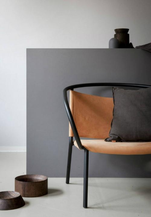 Leuchtend Grau: Vor einer grauen Wand steht ein Ledersessel und Schalen aus dunklem Holz