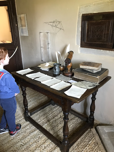 Little boy looking at an edwardian desk covered in papers and books