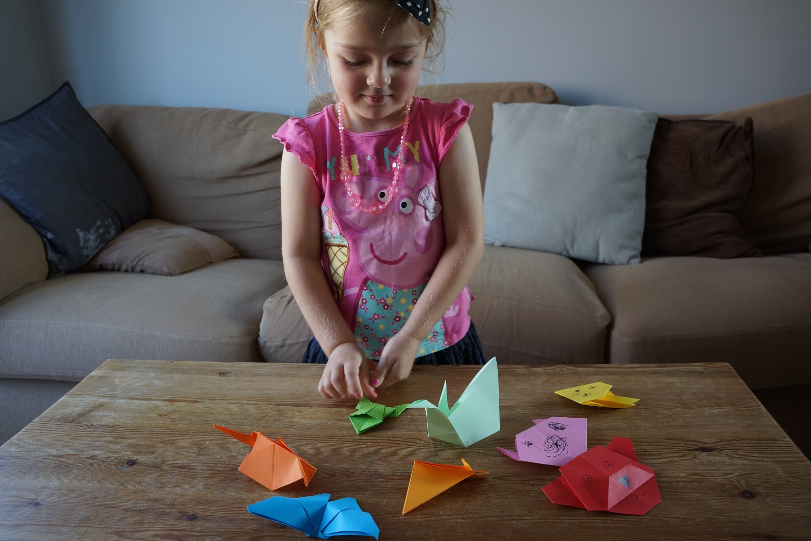 little girl playing with jumping origami frog