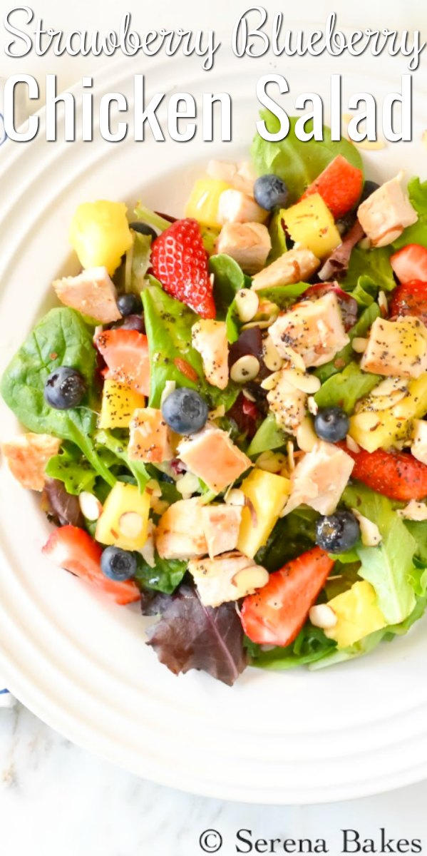 Strawberry Blueberry Pineapple Chicken Salad drizzled with Poppy Seed Dressing on a white plate with writing that says Strawberry Blueberry Chicken Salad.