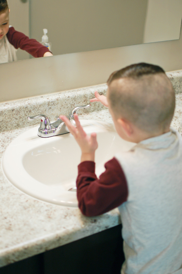 Little boy turns on the faucet to wash his hands after potty training