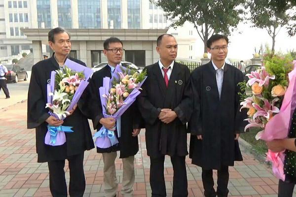 4位辩护律师在天津东丽法院外接受两位当事人母亲的献花。图中从左到右分别是张赞宁、常伯阳、余文生、张科科4位律师。(NTD图片,知情者提供)