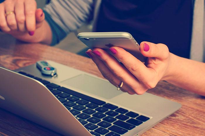 Mulher mexendo em um MacBook com iPhone na mão