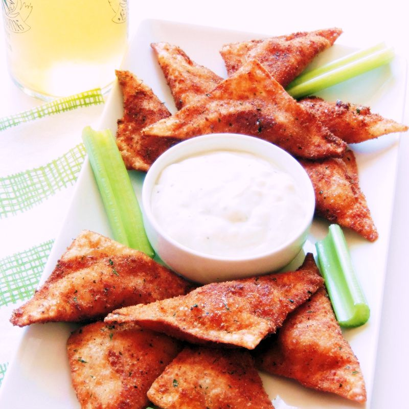 Buffalo Chicken Wontons on a white platter with a green and white towel in the background