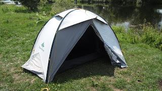 Ein weißes Zelt steht mit offenem Eingang am Ufer eines Flusses