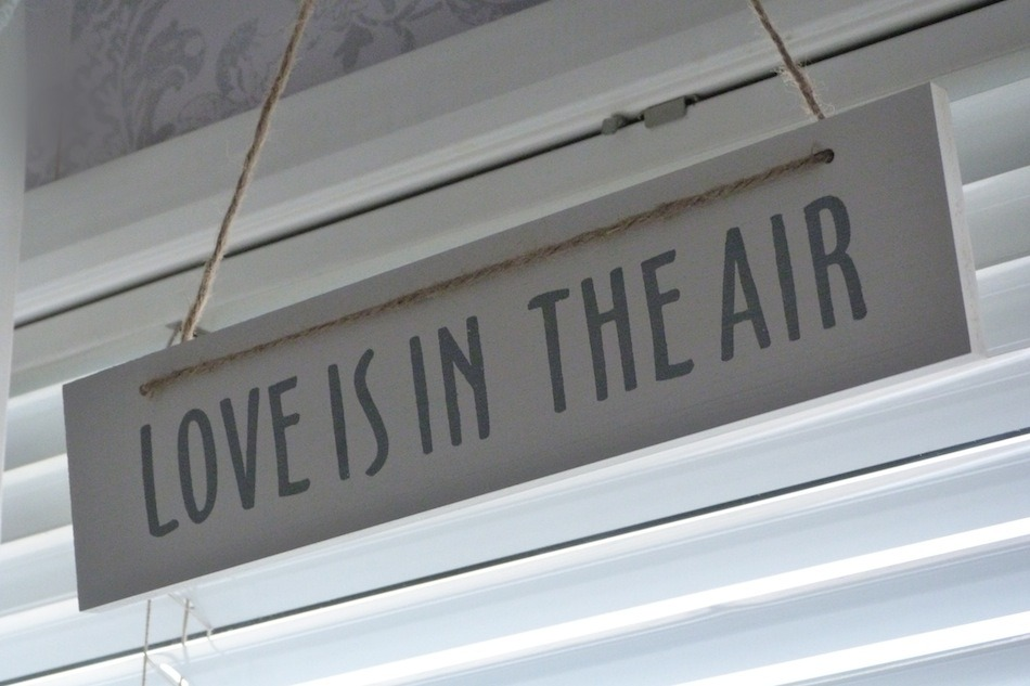 an image of love is in the air wooden sign