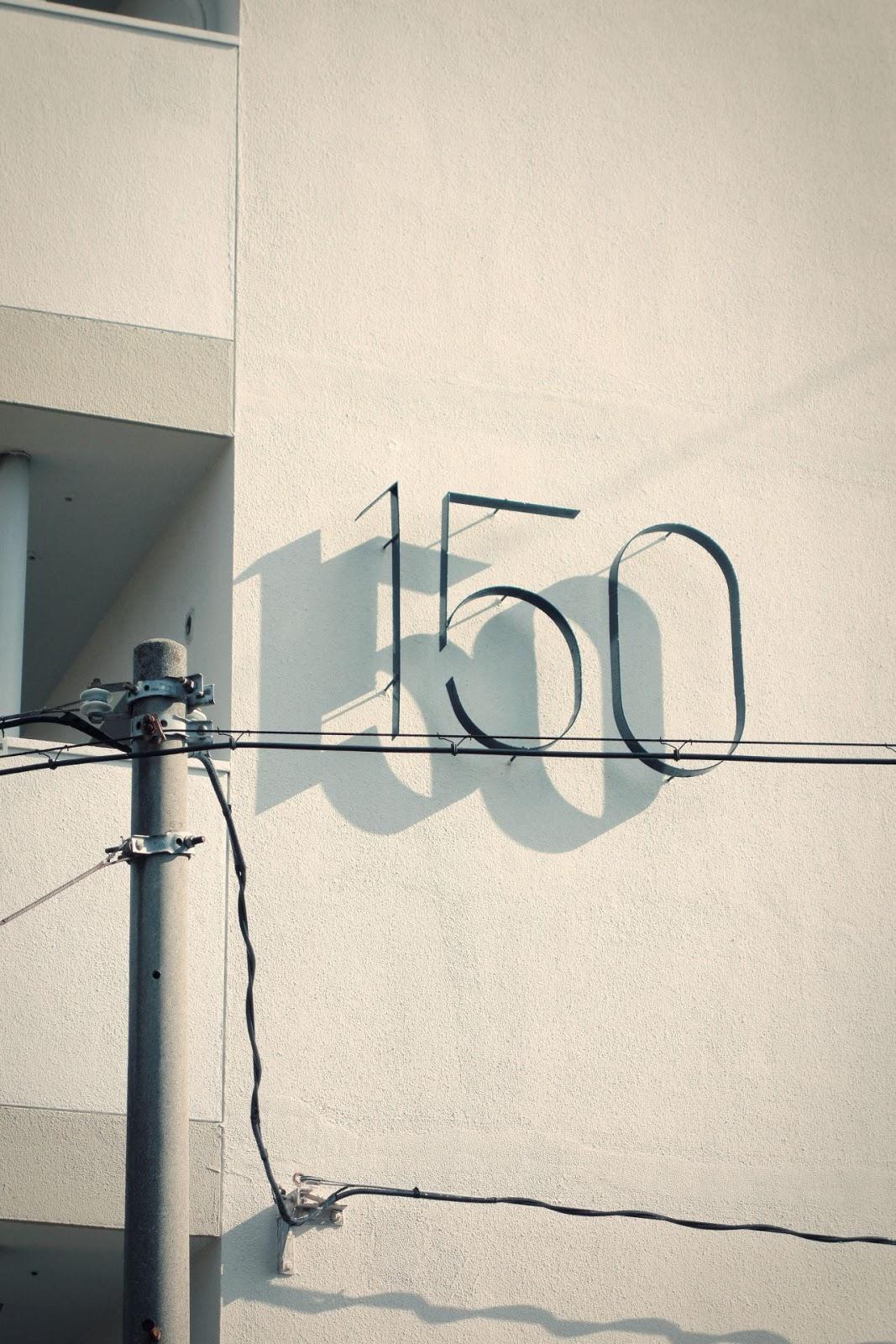 Ombra sobre una paret blanca del número metàl·lic de la casa, el cent cinquanta. Foto artìstica.