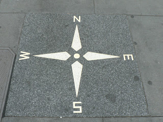 A compass painted on a sidewalk.