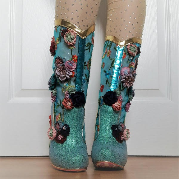 leg tilted in aqua cowboy style sparkly boots