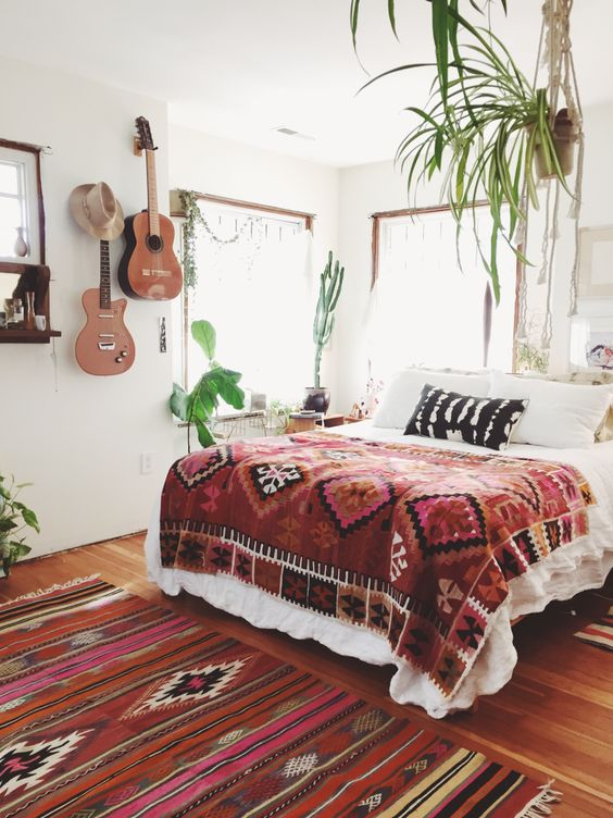 Bohemian bedroom with beautiful rug and plants