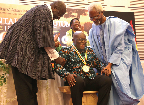 Ambassador Kwesi Quartey (left) and Prof. Atukwei Okai, helping President Akufo-Addo to sit on the PAWA Stool of Royalty