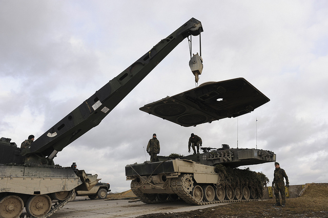 A German recovery vehicle lifts the engine panel from a Leopard 2 main battle tank