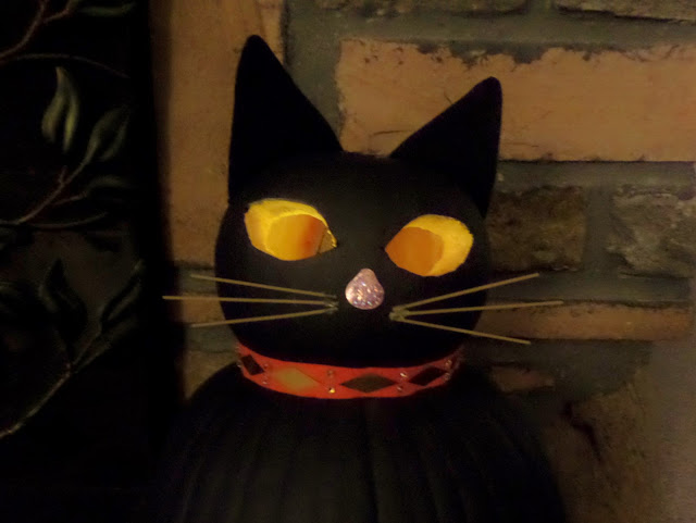 carved black cat with glowing eyes