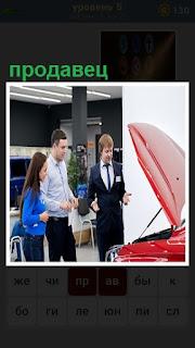 В автосалоне продавец показывает автомобиль на продажу