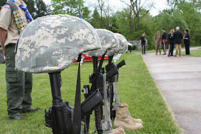 Helmets, boots, and rifles used to make a memorial to fallen soldiers