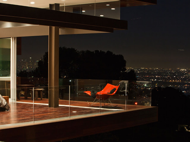 Picture of the red chair on the terrace and city lights in the background
