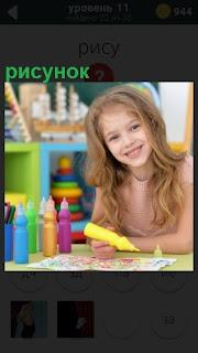 За столом девочка фломастером изобразила рисунок и показывает его