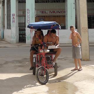 Kuba, Havanna, Stadtteil Centro, Bicitaxi, darin zwei Männer mit nacktem Oberkörper, rauchend, lesend, Musik hörend.