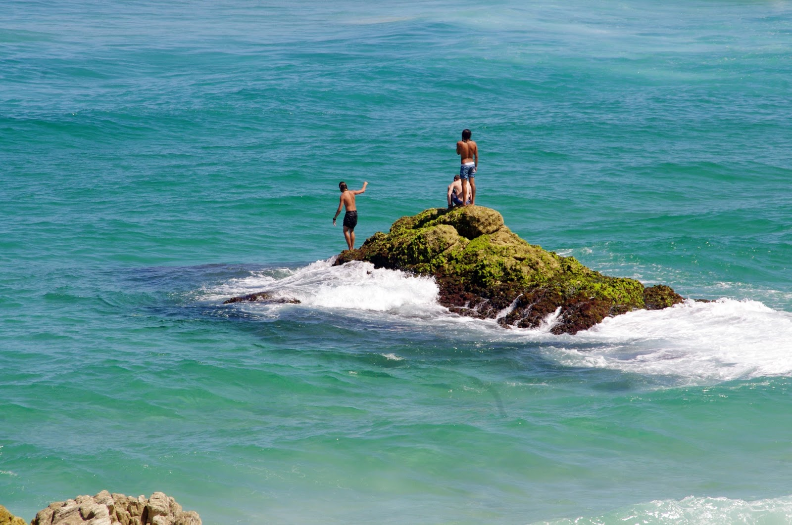 Children playing on rocks in Ocean at Stradbroke Island